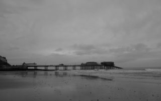 A seaside pier after the tide has gone out in Norfolk, England